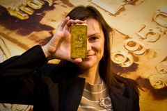 Young woman holding a gold bar royalty free stock photo