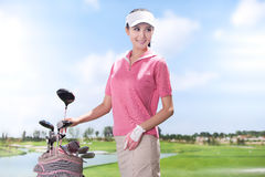 Young woman holding golf clubs Stock Photography