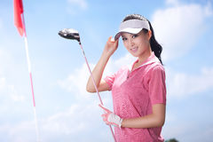 Young woman holding golf clubs Stock Images