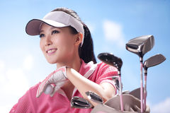 Young woman holding golf clubs Royalty Free Stock Photos