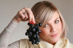 Young woman holding grape. Attractive woman holding a bunch of grapes Stock Images