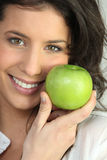 Young woman holding green apple Royalty Free Stock Images