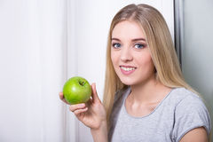 Young woman holding green apple at home Royalty Free Stock Image