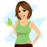 Young woman holding a green apple showing thin waist Royalty Free Stock Photography