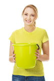 Young woman holding green bucket. Stock Photo