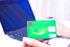 How to pay bills. A young woman holding a green credit card and check the amount in the bank account on a laptop, photography Royalty Free Stock Photos