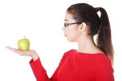 Young woman holding green fresh apple in hand Stock Image