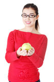Young woman holding green fresh apple in hand Stock Images