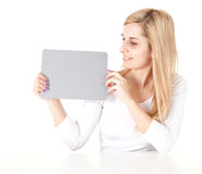 Young woman holding grey card. Young woman leaning on the table holding grey card, white background Stock Photos