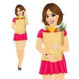 Young woman holding a grocery shopping bag full of food Royalty Free Stock Photos