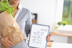 Young woman holding grocery shopping bag with Royalty Free Stock Photography