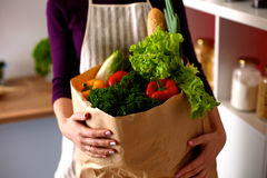 Young woman holding grocery shopping bag with stock photos