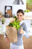 Young woman holding grocery shopping bag with Royalty Free Stock Image