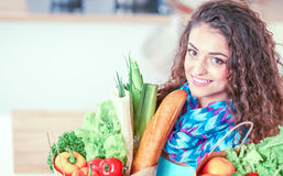 Young woman holding grocery shopping bag with vegetables Standing in the kitchen. Stock Photos