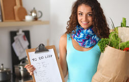 Young woman holding grocery shopping bag with vegetables Standing in the kitchen. Stock Images