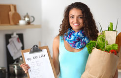 Young woman holding grocery shopping bag with vegetables Standing in the kitchen. Royalty Free Stock Photos