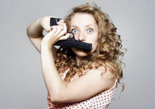 Young woman holding a gun over her mouth Royalty Free Stock Photos