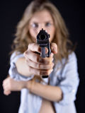 Young woman holding a gun. Young and sexy woman holding a gun Stock Images