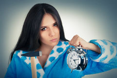 Young Woman Holding a Hammer and an Alarm Clock Royalty Free Stock Photography