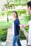 Young Woman Holding Hand Of Boyfriend In Park Stock Photo
