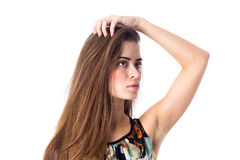 Young woman holding hand on her head. Young attractive woman with long brown hair in colored shirt holding hand on her head on white background in studio Royalty Free Stock Photos