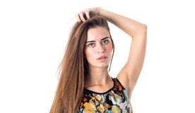 Young woman holding hand on her head. Young beautiful woman with long brown hair in colored shirt holding hand on her head on white background in studio Royalty Free Stock Image