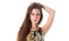 Young woman holding hand on her head. Young pretty woman with long brown hair in colored shirt holding hand on her head on white background in studio Stock Photography