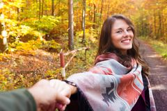 Young woman holding hand of man and walking in forest in autumn. Young brunette woman holding hand of man and walking in forest in autumn Stock Photo