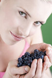 A young woman holding a handful of blueberries Royalty Free Stock Photo