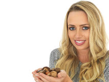 Young Woman holding a Handful of Nuts Royalty Free Stock Photos