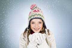 A young woman holding a handful of snow, smiling Stock Photography