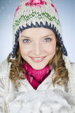 A young woman holding a handful of snow, smiling Royalty Free Stock Photos