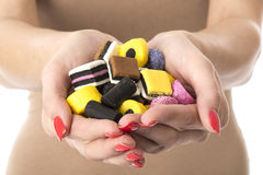 Young Woman Holding a Handful of Sweets Royalty Free Stock Photos
