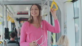 Young woman holding handle while moving in the modern tram. Happy passenger enjoying trip at the public transport. Young woman holding handle while moving in stock video