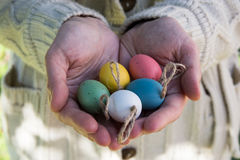 Young woman holding in hands decorative colorful Easter eggs on twine, outdoors, sun flecks. Closeup, kinfolk style, authentic stock image
