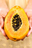 Young woman holding in hands half of ripe juicy papaya, close up Stock Photography