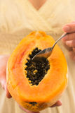 Young woman holding in hands half of ripe papaya, taking out seeds with spoon Stock Images