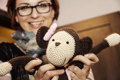 Young woman holding in hands knitted monkey doll Royalty Free Stock Photo