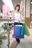 Young woman holding in hands multi-coloured bags Stock Photos