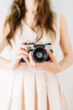 Young woman holding in hands old vintage camera. Girl photographer Stock Photos