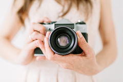 Young woman holding in hands old vintage camera. Girl photographer and film camera stock image