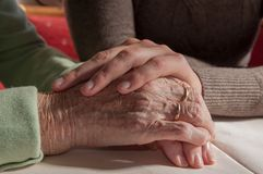 Young woman holding hands of sad senior woman with wheelchair stock photo