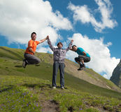 Young woman holding hands with two laughing man on a background of mountains Royalty Free Stock Photos