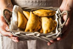 Young woman holding in hands wicker basket with freshly baked empanadas turnover pies with vegetables kinfolk. Young woman holding in hands wicker basket with Stock Images