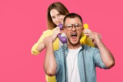 young woman holding handsets and man in eyeglasses screaming isolated