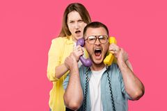 young woman holding handsets and man in eyeglasses yelling isolated