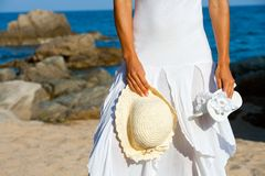 Young woman holding hat and flip flops on beach. Close up of Young woman holding hat and flip flops on beach Stock Photos