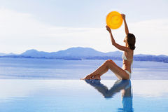 Young woman holding hat like a sun. Beautiful girl enjoying a sun in the infinity pool. Vacations and summer concept Royalty Free Stock Photos