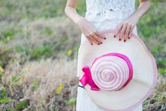 Young woman holding a hat. In the park royalty free stock images