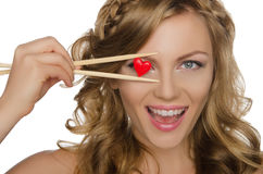 Young woman holding heart with chopsticks Royalty Free Stock Images